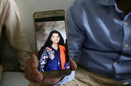 Abdul Aziz Sheikh, center, father of Sabika Sheikh, a victim of a shooting at a Texas high school, shows a picture of his daughter in Karachi, Pakistan, May 19, 2018.