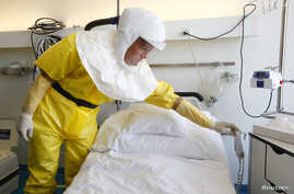 Infection control nurse Heinz Schuhmacher wears a protective suit during a media presentation at an isolation ward for possible Ebola patients at of the Universitaetsspital Basel hospital in Basel,Switzerland, Oct. 15, 2014.