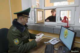 FILE - A Belarussian border guard checks a tourist's passport at a border crossing with Poland, near the village of Pererov, southwest of Minsk, March 31, 2015.