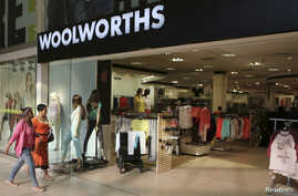 FILE - Shoppers walk into a Woolworths store at a shopping center in Lenasia, south of Johannesburg, August 2013.