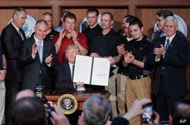 President Donald Trump, accompanied by coal miners and, from left, Interior Secretary Ryan Zinke, EPA Administrator Scott Pruitt, second from right, Energy Secretary Rick Perry, and Vice President Mike Pence, far right, holds up the signed Energy Ind