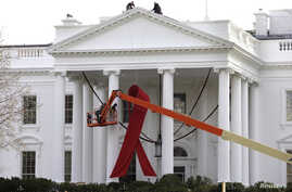 A large red ribbon is installed on the North Portico of the White House to mark World AIDS Day on December 1, in Washington, D.C., November 30, 2012.