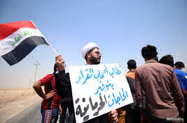 "A protester holds a sign that reads ""We ask the decision makers to provide the things we are deprived of"" during a protest in south of Basra, Iraq July 16, 2018."