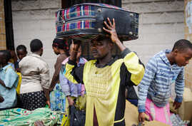 Kadogo Ombeni, 27, stands near the Rwandan border with Congo with a suitcase on his head after fleeing his home in the Bujovu Kabutembo district of Goma, in the east of the Democratic Republic of the Congo, November 20, 2012.