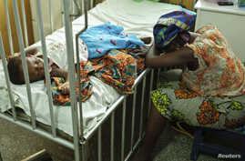 Hassana Ousmane rests her head against the bed where her 21-month-old daughter, Zeinab, suffering from malaria, rests at the Princess Marie Louise Children's Hospital in Accra, Ghana, April 25, 2012.