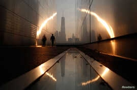 A man walks through the 9/11 Empty Sky memorial at sunrise across from New York's Lower Manhattan and One World Trade Center in Liberty State Park in Jersey City, New Jersey, September 11, 2013. Americans will commemorate the 12th anniversary of the