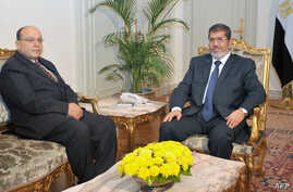 Egyptian President Mohamed Morsi (R) is seen with Prosecutor General Talaat Abdullah in file photo released my Morsi's office November 22, 2012.