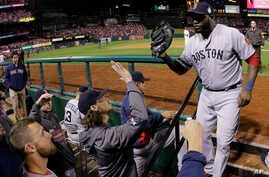 Boston Red Sox designated hitter David Ortiz, right, is greeted in the dugout after being pulled from the game during the eighth inning of Game 5 of baseball's World Series against the St. Louis Cardinals, Oct. 28, 2013