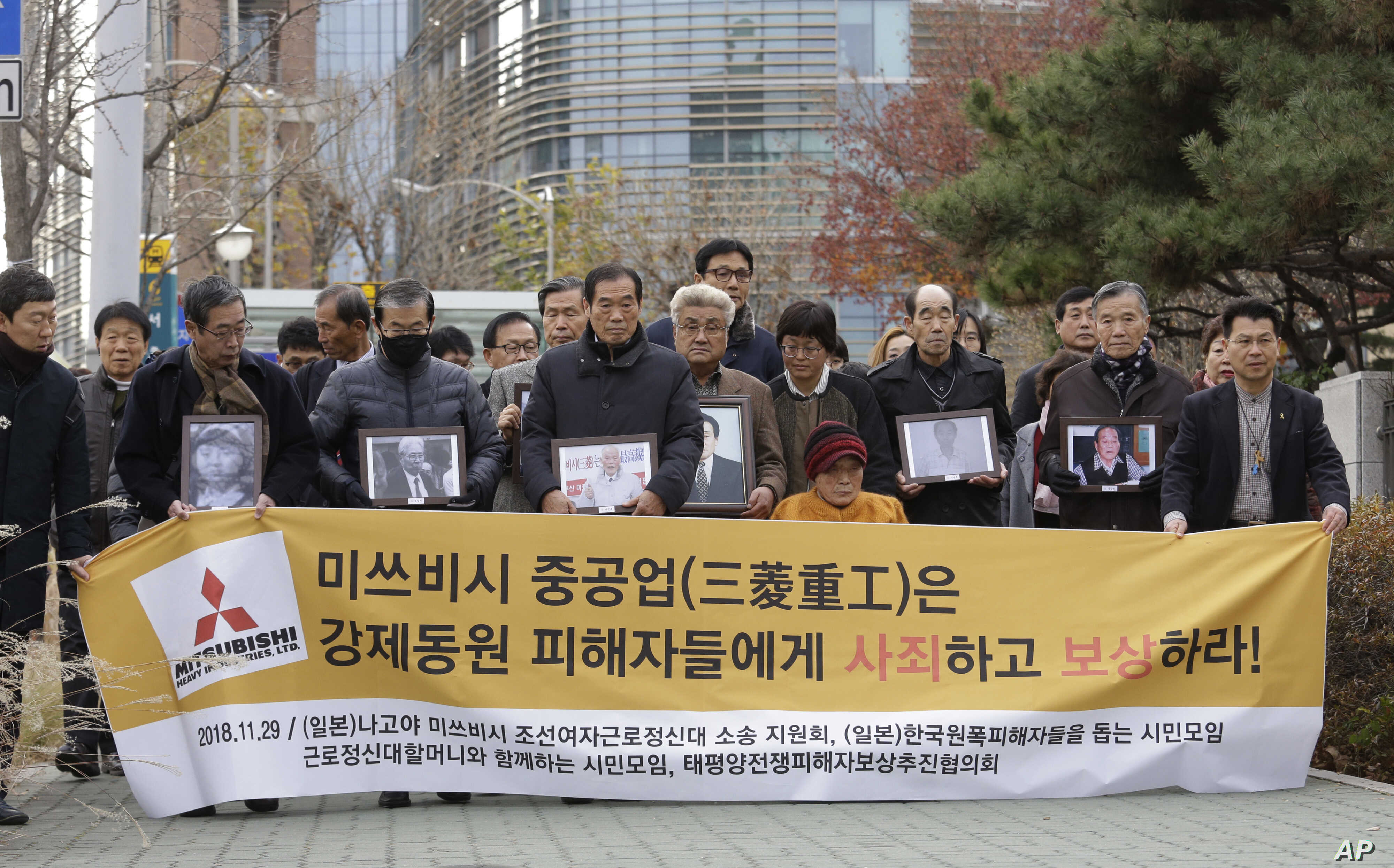 "Victims of Japan's forced labor and their family members arrive at the Supreme Court in Seoul, South Korea, Nov. 29, 2018. The sign reads "" Mitsubishi Heavy Industries apologize and compensate victims."""