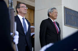 Secretary of Defense Ash Carter and Singapore's Minister of Defense Ng Eng Hen, listen as the national anthem of Singapore and the United States are played during an honor cordon at the Pentagon, Dec. 7, 2015.