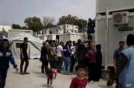 FILE - Migrants and refugees wait outside UNHCR offices for their papers, inside the camp of Moria on Lesbos, Greece.