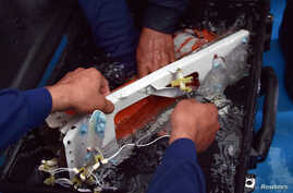 Indonesian divers hold the flight data recorder of AirAsia QZ8501 onboard the navy vessel KRI Banda Aceh, in the Java Sea, Jan. 12, 2015.