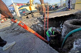 Workers fix a sewer main below the sidewalk in Mid City New Orleans, Jan. 31, 2018. City officials say New Orleans needs more than $11 billion to update key parts of its infrastructure.