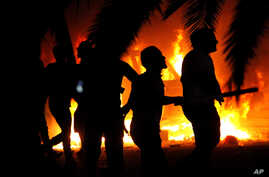 FILE - Libyan civilians watch fires at an Ansar al-Shariah Brigades compound, after hundreds of Libyans, Libyan Military, and Police raided the Brigades base, in Benghazi, Libya, Sept. 21, 2012.