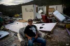 Luis Cosme poses sitting in an armchair in what is left of his house destroyed by Hurricane Maria, in Morovis, Puerto Rico, Oct. 1, 2017.