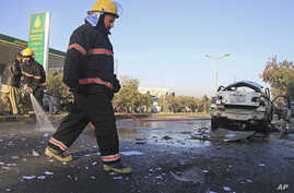 Afghan firefighters clear the site of a blast that killed a provincial judge in Jalalabad, capital of Nangarhar province, Afghanistan Wednesday, Jan. 7, 2015.