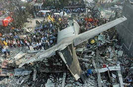 Rescuers search for victims at the site where an air force cargo plane crashed in Medan, North Sumatra, Indonesia, Tuesday, June 30, 2015. The Hercules C-130 plane crashed into a residential neighborhood in the country's third-largest city Medan. (AP