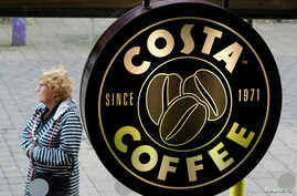 FILE - A woman walks past a Costa Coffee in Loughborough, Britain, April 25, 2018.