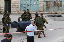 Israeli soldiers carry the dead body of one of two Palestinians, whom the Israeli military said were shot dead by Israeli troops after they attacked a soldier, in Tal Rumaida in the West Bank city of Hebron, March 24, 2016.