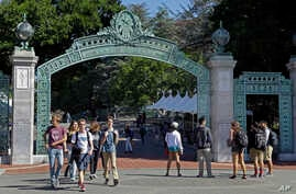 FILE - In this April 21, 2017 file photo, students walk past Sather Gate on the University of California, Berkeley campus in Berkeley, Calif.