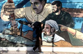 FILE- An Iranian woman walks past a mural portraying Iranians' solidarity against their enemies, painted on the wall of a government building at the Felestin (Palestine) Sq. in downtown Tehran, July 30, 2018.