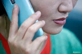 FILE - A North Korean defector living in South Korea uses her mobile phone during an interview at her office in Seoul.