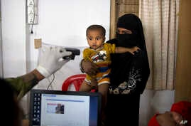 FILE - A Bangladeshi officer takes the photograph of a Rohingya boy while his mother holds him during the process of registration at Kutupalong refugee camp near Cox's Bazar, Bangladesh, Jan. 16, 2018.