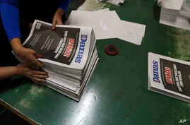 """Pressroom workers pack an edition of the newspaper Danas in Belgrade, Serbia, Sept. 27, 2017. The paper bears a white inscription that warns: """"This is what it looks like when there is no free press!"""""""