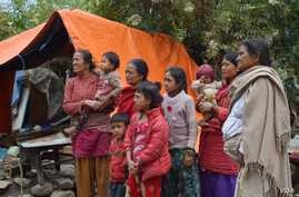A family stands next to a tent in front of their destroyed home. They prefer to stay here instead of sheltering in a school because they are worried about their valuables being plundered from the rubble, Sankhu, Nepal, April 29, 2015. (Steve Herman/V