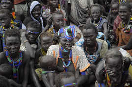 Victims of ethnic violence in Jonglei, South Sudan, wait in line at the World Food Program distribution center in Pibor, South Sudan to receive emergency food rations, Thursday, Jan.12, 2012.