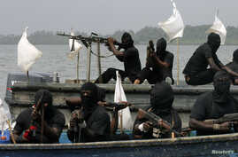 FILE - Militants are seen patrolling the creeks of the Niger delta region of Nigeria, Jan. 30, 2007.