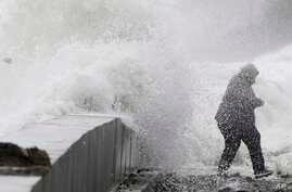 A woman gets caught by a wave as heavy seas continue to come ashore in Wintrhrop, Mass., March 3, 2018, a day after a nor'easter pounded the Atlantic Coast with hurricane-force winds and sideways rain and snow.