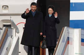 Chinese President Xi Jinping (L) and First Lady Peng Liyuan wave as they disembark from a plane upon their arrival at Moscow's Vnukovo airport, March 22, 2013.