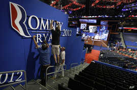 Workers place a Romney-Ryan campaign sign inside of the Tampa Bay Times Forum at the Republican National Convention in Tampa, Florida, Sunday, Aug. 26, 2012.