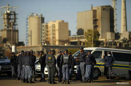 Police officers stand outside the Lonmin mine in Rustenburg, South Africa, May 14, 2014.