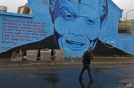 FILE - A woman walks past a mural with the face of former South African President Nelson Mandela in Cape Town, South Africa, July 18, 2014.