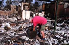 Local resident Alan Seaman looks inside a safe in the remains of his home that was destroyed by a fire in the Blue Mountains suburb of Winmalee, west of Sydney, Oct. 21, 2013.