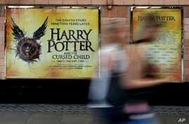 Pedestrians pass a poster advertising the new Harry Potter play at the Palace Theatre in London.