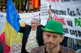 "Romania Canada Gold Mine Protest: FILE -A man holding a banner that reads ""Stop the Rosia Montana siege""  shouts during a protest in Bucharest, Romania, in this Sunday, Sept. 22, 2013 file photo."