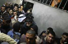 Palestinians gather as the body of Abdullah Mohana, Islamic Jihad militant, is brought to the morgue of the Nasser hospital in Khan Younis, southern Gaza Strip, Saturday, Nov. 5, 2011.