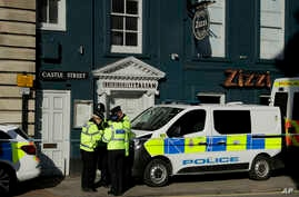 Police officers stand outside a Zizzi restaurant in Salisbury, England, Wednesday, March 7, 2018, near to where former Russian double agent Sergei Skripal was found critically ill.