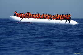 Migrants on a rubber dinghy wait to be rescued by the Migrant Offshore Aid Station (MOAS) ship MV Phoenix, some 20 miles (32 kilometres) off the coast of Libya, August 3, 2015. Some 118 migrants were rescued from a rubber dinghy off Libya on Monday m