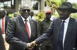 South Sudan's First Vice President Riek Machar, left, and President Salva Kiir, right, shake hands following the first meeting of a new transitional coalition government, in the capital Juba, April 29, 2016.