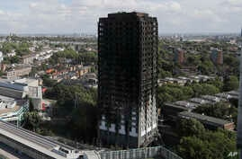 The scorched facade of the Grenfell Tower in London, Thursday, June 15, 2017, after a massive fire raced through the 24-storey high-rise apartment building in west London early Wednesday.