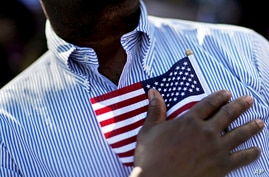 A candidate for citizenship holds the American flag against his chest in Atlanta.