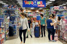 FILE - Shoppers browse at a Toys R Us store in Miami, Nov. 25, 2016. The toys your kids unwrap this Christmas could invite hackers into your home. That Grinch-like warning comes from the FBI, which said this summer that toys connected to the internet