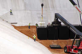 FILE - Crews from Waste Control Specialists load the first of two containers with low-level radioactive waste from Los Alamos National Laboratory in New Mexico.