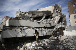 Men walk on the rubble of the Chamber of Trade and Industry headquarters after it was hit by a Saudi-led airstrike in Sanaa, Yemen, Tuesday, Jan. 5, 2016.