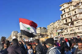 A young boy waves the Syrian flag as residents in a government-held area of Aleppo gather in the street during an evacuation operation of rebel fighters and their families from rebel-held neighborhoods in Syria's northern embattled city on Dec. 15, 2