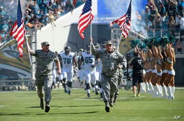Military personnel lead the Jacksonville Jaguars players onto the field during player introductions before an NFL football game against the Miami Dolphins in Jacksonville, Fla., Sunday, Sept. 20, 2015.